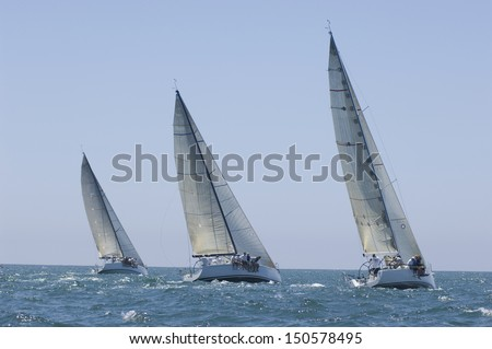 View of three yachts compete in team sailing event - stock photo