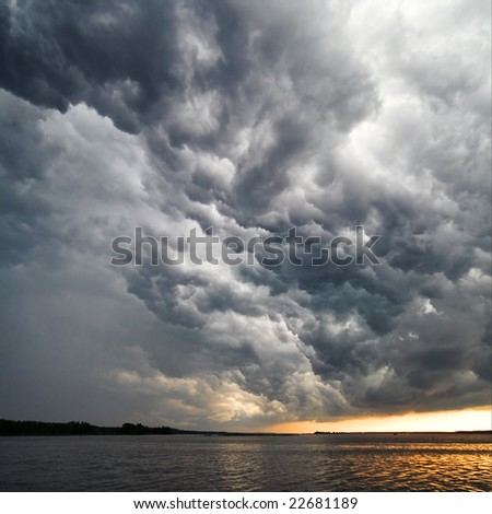 View of thunderstorm clouds above water - stock photo
