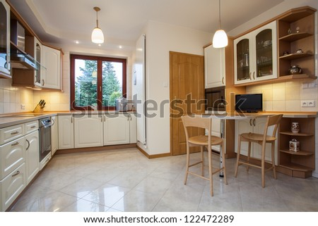 View of traditional kitchen in beige color with television - stock photo
