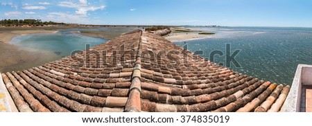 View of traditional rooftops of the Algarve region next to Ria Formosa marshlands, Portugal. - stock photo