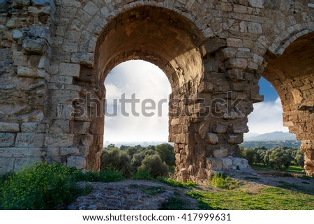 View of Tralleis Ancient City in Aydin, Turkey, stone ruins from 2nd century on cloudy blue sky background. - stock photo