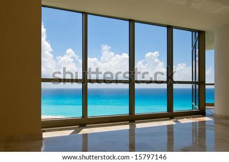 View of tropical beach through hotel windows - stock photo