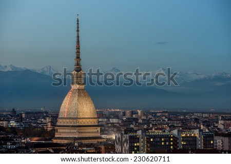 View of Turin at twilight with the illuminated Mole Antonelliana and the snow capped peaks of the Alps on the background. - stock photo