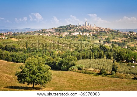 View of Tuscan village San Gimignano with fields, meadows and vineyards - stock photo