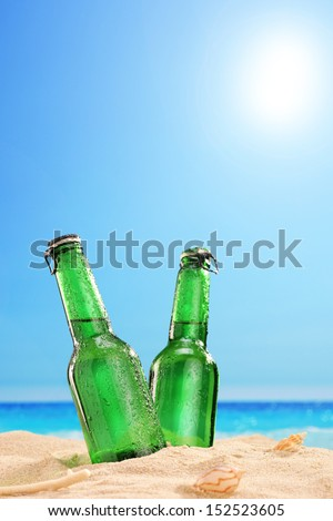 View of two beer bottles on a sandy beach, with clear sky and sun, next to a sea - stock photo