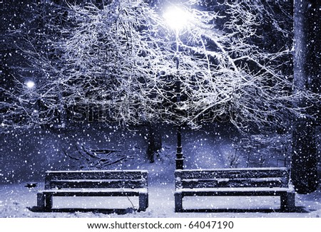 View of two benches and shining lantern through snowing. Blue tone. Night shot. - stock photo