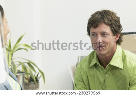 View of two businesspeople having a discussion in office setting - stock photo