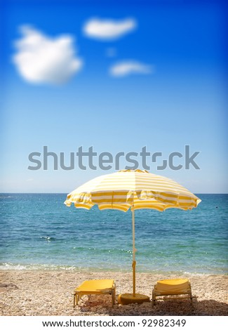 view of two chairs and umbrella on the beach - stock photo