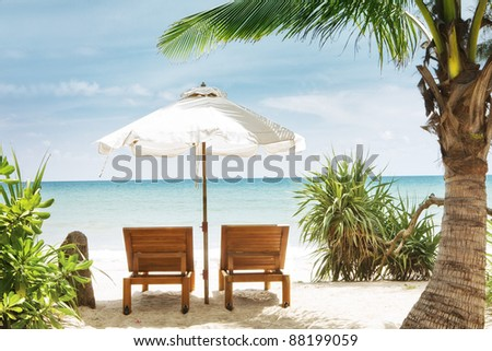 view of two chairs and  white umbrella on the beach - stock photo
