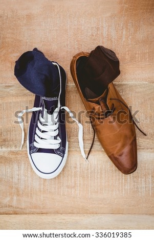 View of two different shoes on wood plank