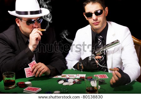 View of two gangster males playing some poker and smoking Cuban cigars. - stock photo