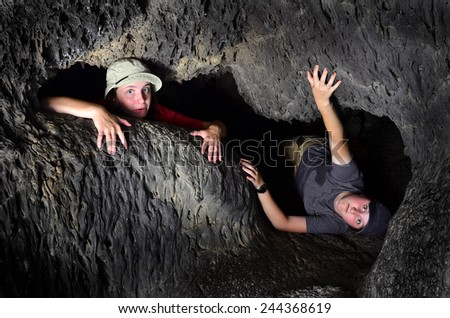 View of two kids exploring inside cave rocks - stock photo