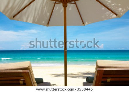 view of two nice chairs and umbrella on tropical beach - stock photo