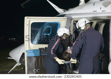 View of two paramedics pushing a victim on a gurney into a rescue helicopter - stock photo