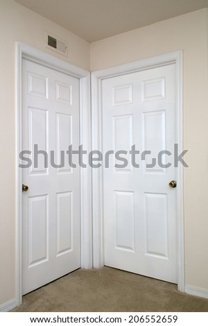 View of two white interior doors closed in carpeted room. - stock photo