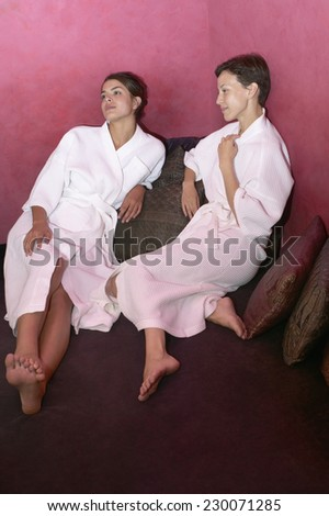 View of two young women talking as they relax in bathrobes - stock photo