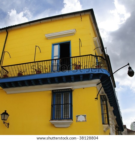 View of typical old havana building with balcony against blue sky - stock photo
