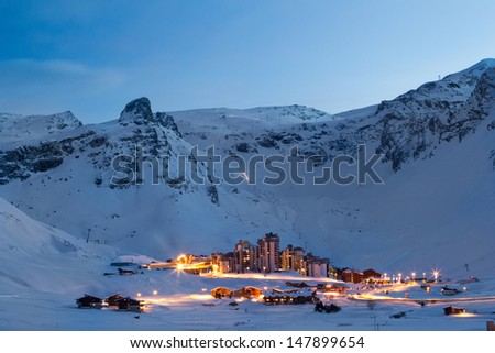 View of Val Claret from Tignes Le Lac at night. Light trails can be seen from traffic passing through Val Claret, and also from machines on the mountain grooming pistes.