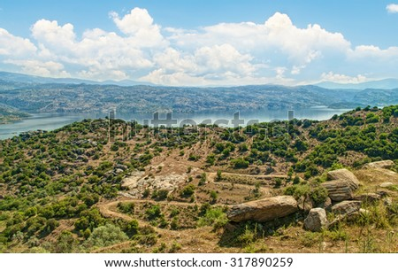 view of valley and lake on sunny day against blue sky with white clouds with big rocks at foreground and trees, Turkey - stock photo