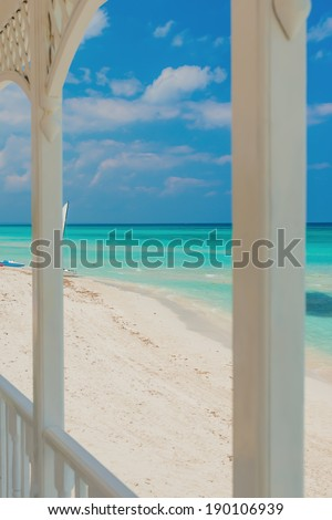 View of Varadero beach in Cuba framed by the columns of a beautiful wooden terrace (focused on the beach) - stock photo