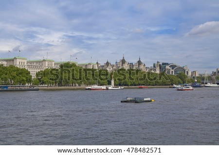 View of Victoria Embankment in London, England across Thames river