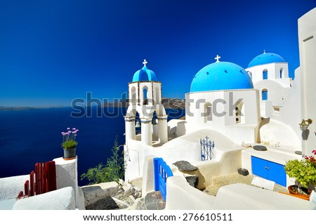 View of volcanic caldera and beautiful village of Oia with its whitewashed blue domed churches of Ag. Spyridonas and Ag. Anastasis, Oia, Santorini, Greece, Europe
