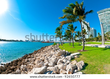 View of waterway used to enter Miami Seaport with city in the background and recreational park at the side - stock photo
