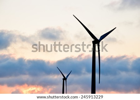 view of wind turbine against partly cloudy blue sky - stock photo