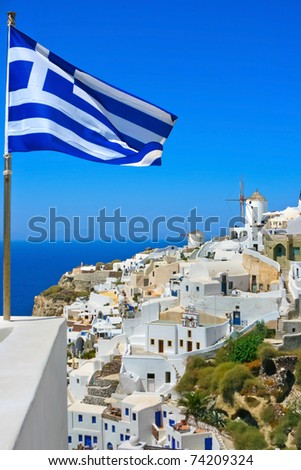 View of windmills with Greece flag in Oia village on island of Santorini, Greece - stock photo