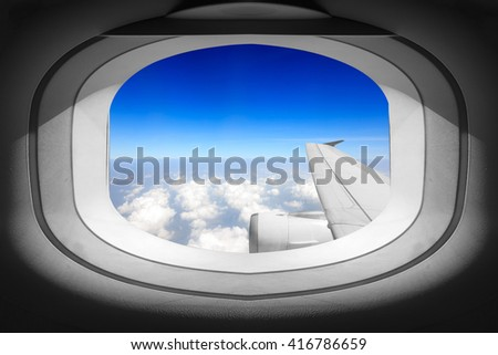 View of window airplane with wing and blue sky atmosphere - stock photo