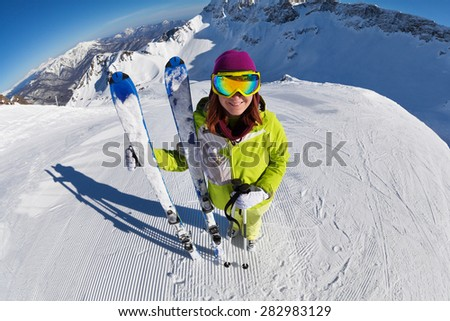 View of woman in mask standing and holding ski and ski poles during sunny winter day on Krasnaya polyana ski resort and Caucasus mountains in Sochi, Russia - stock photo