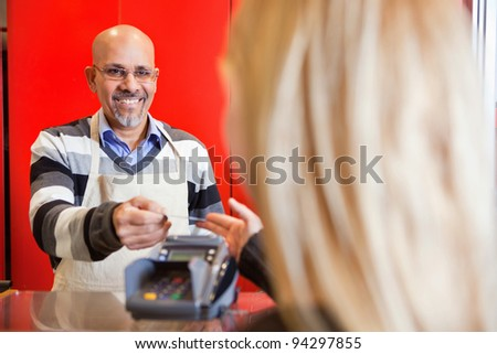 View of woman passing over credit card to shop assistant after shopping - stock photo