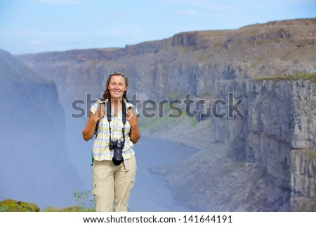 View of woman photographer standing near famous Dettifoss waterfall in Vatnajokull National Park, Northeast Iceland - stock photo