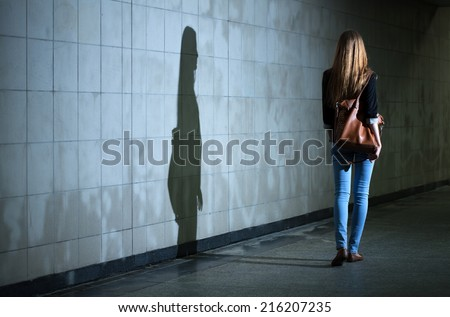 View of woman walking alone at night - stock photo