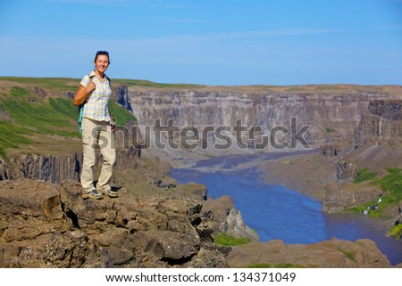 View of woman walking near famous Dettifoss waterfall in Vatnajokull National Park, Northeast Iceland - stock photo