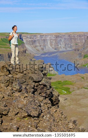 View of woman walking near famous Dettifoss waterfall in Vatnajokull National Park, Northeast Iceland?. Vertical view - stock photo