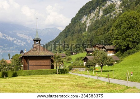 View of wooden church with a lake and mountain at switzerland - stock photo