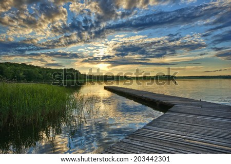 View of wooden jetty on beautiful lake before sunset, Mazury, Poland - stock photo