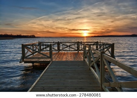 View of wooden jetty on beautiful lake during sunset, Mazury, Poland - stock photo