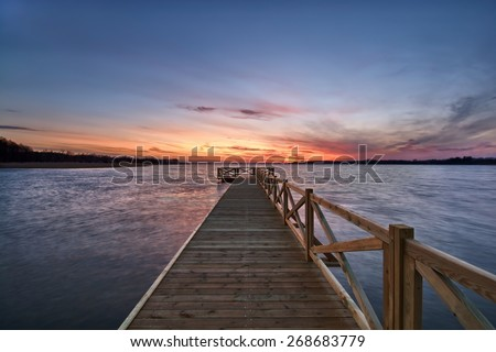 View of wooden jetty on beautiful lake just after sunset, Mazury, Poland - stock photo