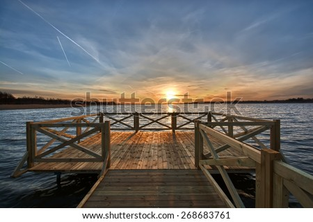 View of wooden jetty on beautiful lake just before sunset, Mazury, Poland - stock photo