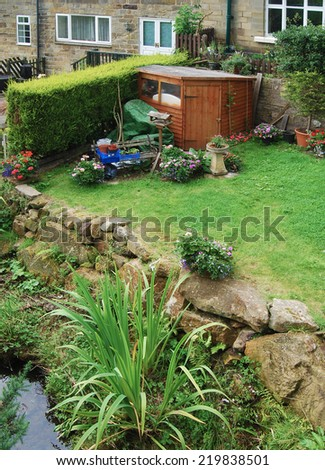 View of wooden shed in garden of terraced house - stock photo