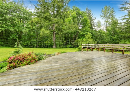 View of wooden walkout deck with patio area. Backyard garden with green lawn.