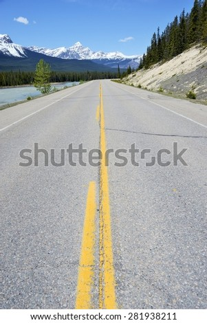 View of Yellow Lines on Highway Stretching Toward Snow-Capped Rocky Mountains