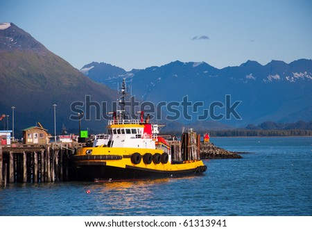 View of yellow tug boat tied up at docks in Valdez, Ak - stock photo