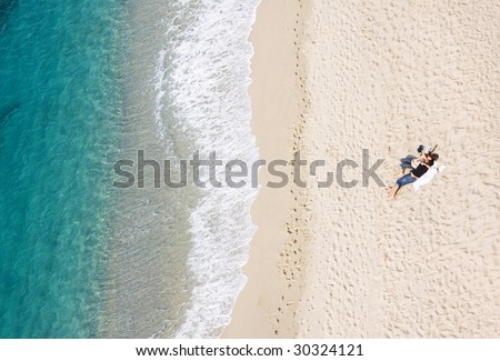 View of young couple resting on tropical beach, lots of copyspace - stock photo