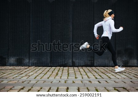 View of young woman running on sidewalk in morning. Health conscious concept with copy space. - stock photo