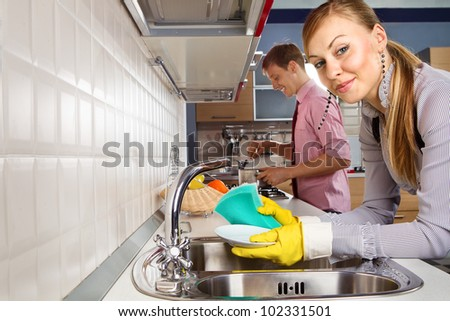 View of  young woman washing dishes and  man cooking at her in kitchen - stock photo
