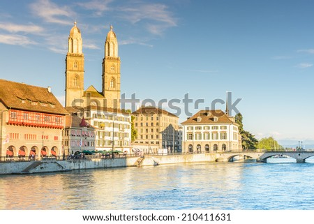 View of Zurich in the evening sunlight/golden hour, Switzerland with the Romanesque-style Protestant Grossmunster church. It is one of the three major churches in the city - stock photo