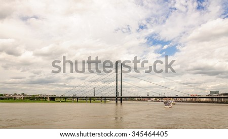 View on a bridge across the Rhine, blue sky with dark clouds near the promenade and the historical part of the Dusseldorf, Germany - stock photo